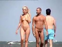 Nude couple filmed walking along the beach, nice blonde with cute bazookas and shaved pussy.