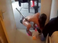 Slender bare wife hoovering apartment wearing just a couple of pink slippers.