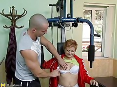 Watch this hawt red headed cougar who takes advantage of this youthful gym instructor. She has great sex experience and starts seducing him, like this babe well knows. This old chick has all this babe needs to make a fellow happy. She starts taking off her clothing to turn the youthful stud on. He likes playing with her tits.