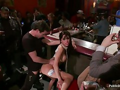 Gia DiMarco is on a rope leash, getting fucked in the wazoo right in the middle of the bar while the patrons watch. This hottie continuously thanks James Deen for fucking her ass. Then she's on the floor, getting fingered by a woman, squirting all over. This hottie mops up the mess with Gia's hair, then fists her.